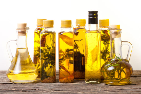 Assortment of spicy oils with herbs and spices in different bottles over white background