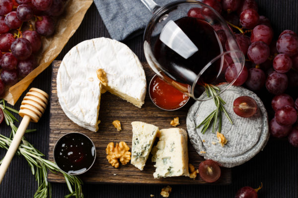 Cheese plate served with wine, jam and honey top view